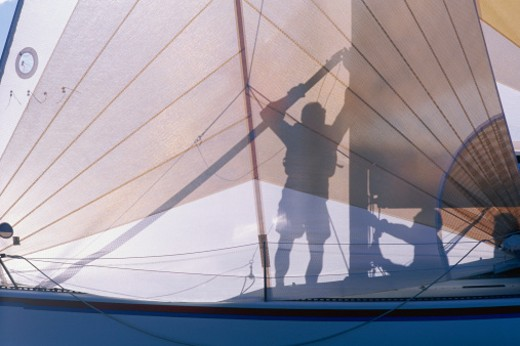 Stock Photo: 1491R-1042980 Silhouette of two men preparing sail on sailboat