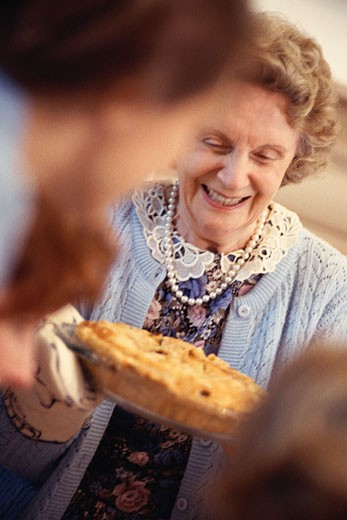 Stock Photo: 1491R-1047046 Woman bringing freshly baked pie to group of people