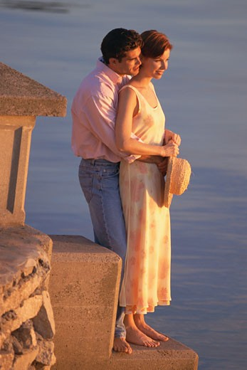 Man and woman overlooking water : Stock Photo