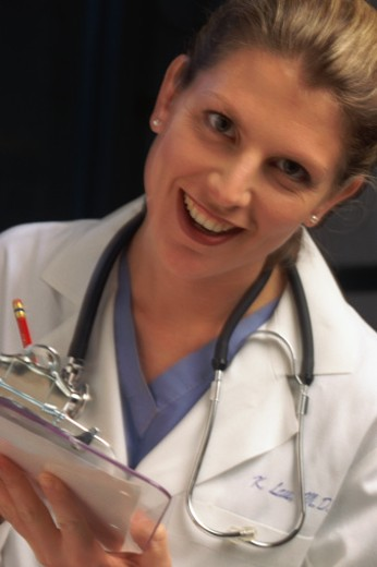 Stock Photo: 1491R-1050336 Female doctor holding clipboard and smiling