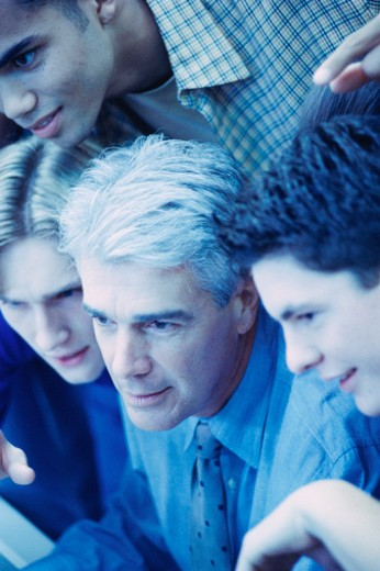 Students gathered around teacher, all looking in same direction : Stock Photo