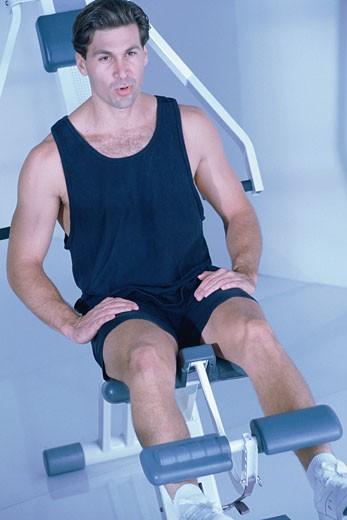 Man using weight machine : Stock Photo