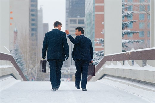 Businessmen on snowy walkway : Stock Photo