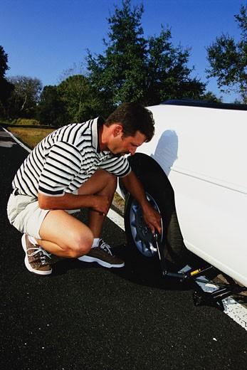 Man changing flat tire : Stock Photo