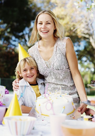 Mother and son (6-8) at birthday celebration in garden, smiling : Stock Photo
