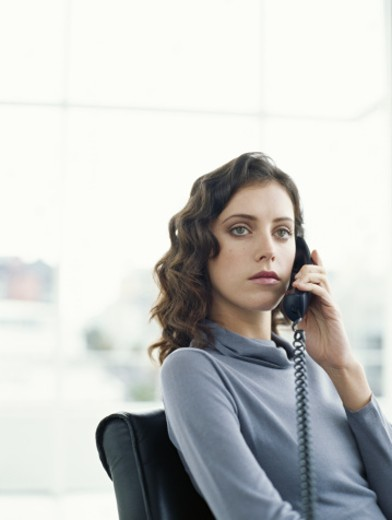 Young woman sitting in office using telephone (focus on woman) : Stock Photo