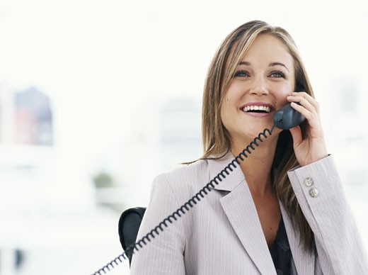 Stock Photo: 1491R-1062800 Young businesswoman using telephone in office, smiling