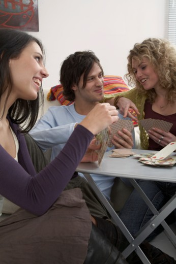 Stock Photo: 1491R-1062857 Young adults playing cards, close-up
