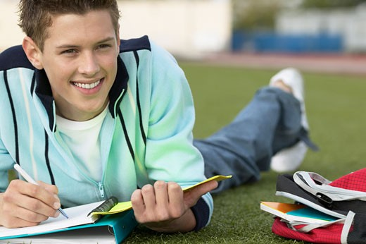 teenage boy (16 - 18) lying on the grass writing : Stock Photo