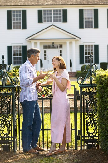 man and woman standing outside a house toasting with wine : Stock Photo
