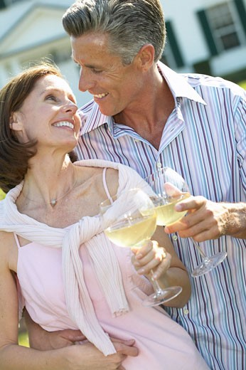 man and woman standing outside a house holding wine glasses : Stock Photo