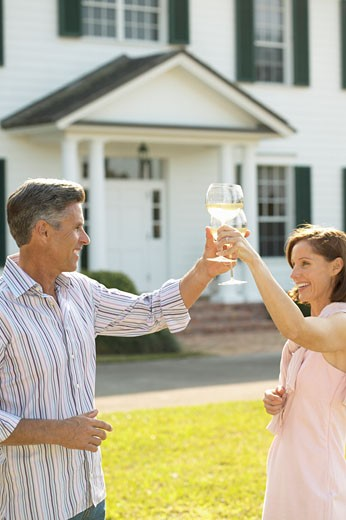Stock Photo: 1491R-1063060 man and woman standing outside a house holding wine glasses