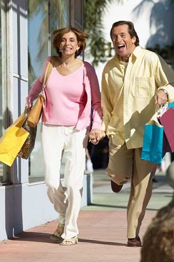 couple running down a street holding shopping bags : Stock Photo