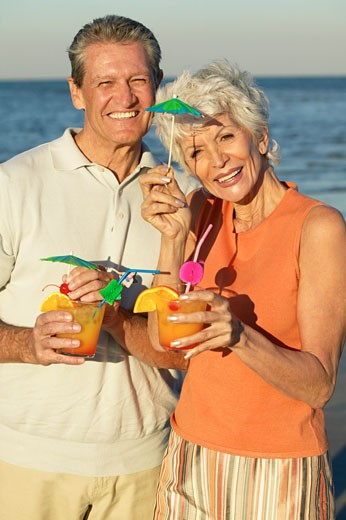 portrait of husband and wife holding cocktails on beach : Stock Photo