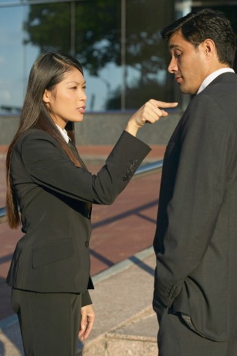 side view of a businesswoman poking a businessman with her finger : Stock Photo
