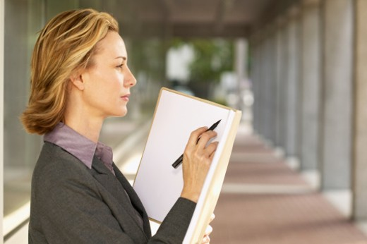 side view of a businesswoman holding a folder looking thoughtful : Stock Photo