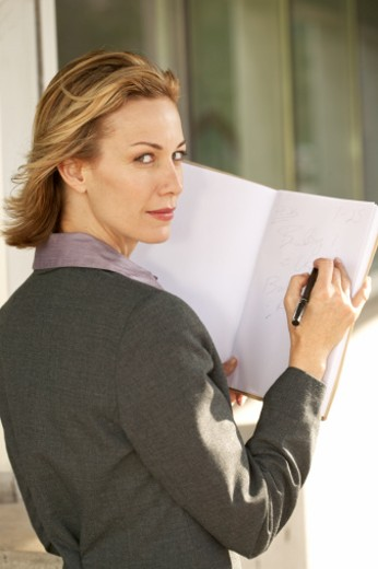 portrait of a businesswoman writing in a folder : Stock Photo