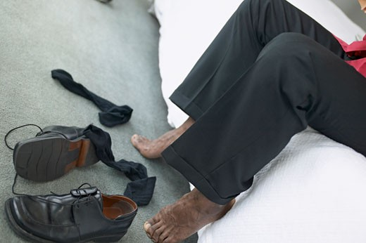 elevated low section view of a mans bare feet with his shoes and socks on the floor in front of him : Stock Photo