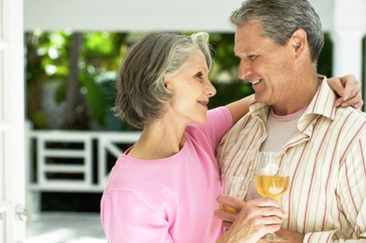 husband and wife embracing while holding glasses of wine : Stock Photo