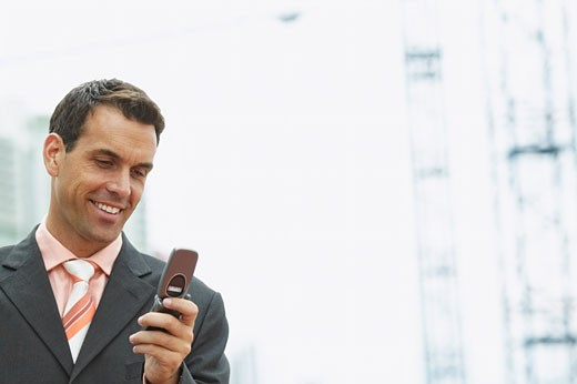 low angle close up view of a businessman looking at his mobile phone : Stock Photo