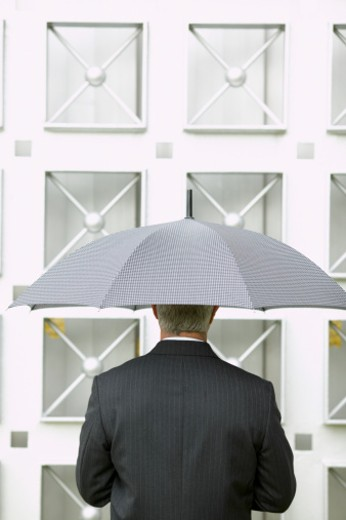 rear view of a businessman holding an umbrella over his head : Stock Photo