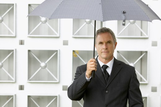 portrait of a businessman holding an umbrella over his head : Stock Photo