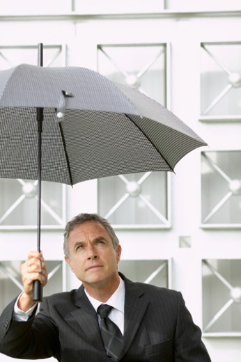 businessman holding an umbrella over his head : Stock Photo