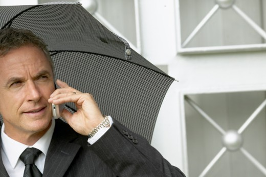 Stock Photo: 1491R-1063595 close up of a businessman holding an umbrella over his head while talking on a mobile phone