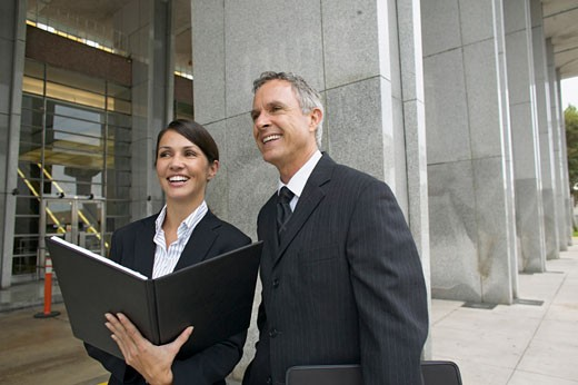 Stock Photo: 1491R-1063603 Businesswoman holding a file and businessman standing beside her