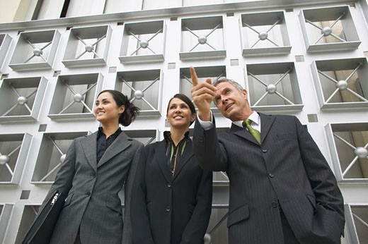Low angle view of three business executives standing and businessman pointing his finger : Stock Photo