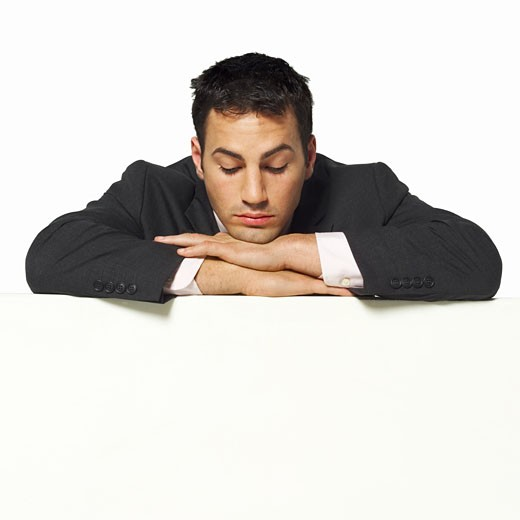 Close-up of young businessman leaning on partition : Stock Photo