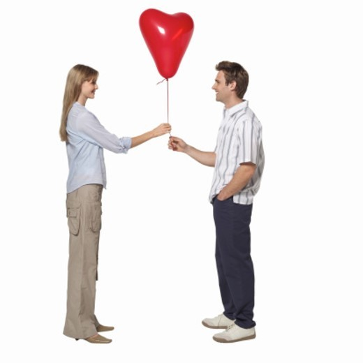 Side view of young couple holding heart shape balloon : Stock Photo