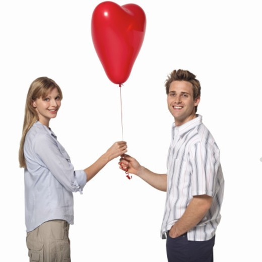 Stock Photo: 1491R-1063866 Close-up of young couple holding heart shape balloon
