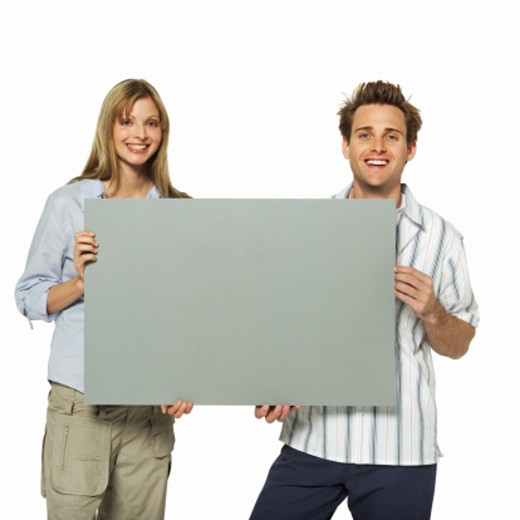Stock Photo: 1491R-1063876 Front view of couple holding blank cards