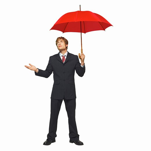 front view portrait of a businessman holding an umbrella while holding his hand out : Stock Photo