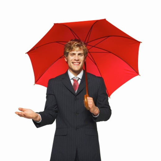 close-up portrait of a businessman holding an umbrella while holding his hand out : Stock Photo