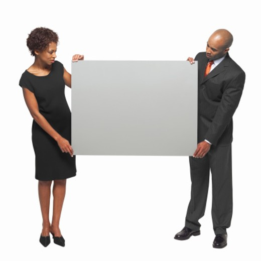 Portrait of businessman and businesswoman holding blank placard between them : Stock Photo