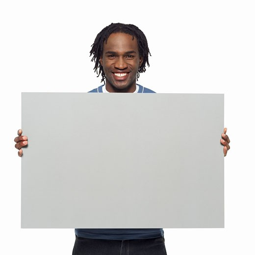 Portrait of young man holding blank card : Stock Photo