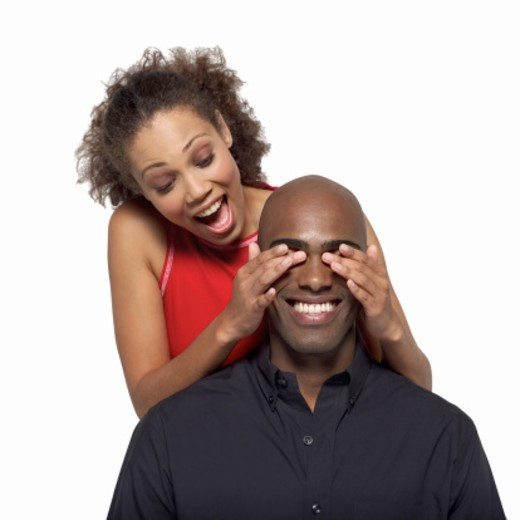 Close-up of young woman covering young man's eyes with hands : Stock Photo