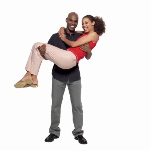Young man holding young woman in his arms : Stock Photo