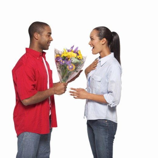 Side view of young man giving young woman bouquet of flowers : Stock Photo
