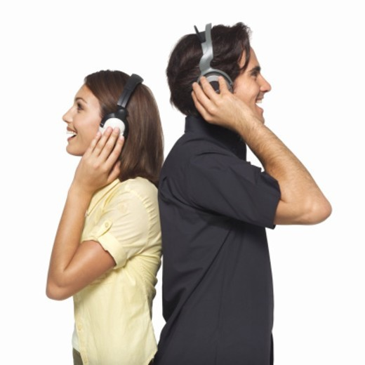 Stock Photo: 1491R-1064286 Side view of young couple wearing headphones
