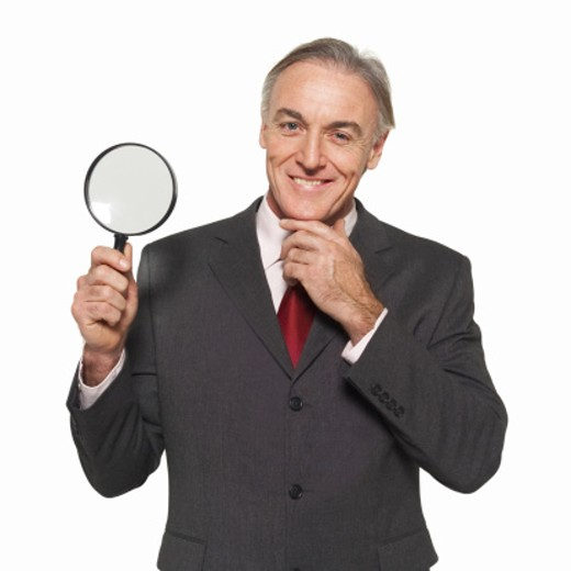 Close-up of businessman holding magnifying lens : Stock Photo