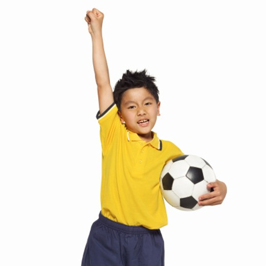 Stock Photo: 1491R-1064795 front view portrait of a boy (10-11) holding a soccer-ball with her hand raised