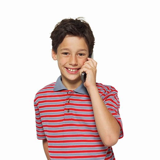 Front view portrait of a boy (11-12) talking on mobile phone : Stock Photo