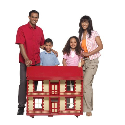 Portrait of parents with their daughter (11-12) and son (10-11) standing with a dolls house : Stock Photo