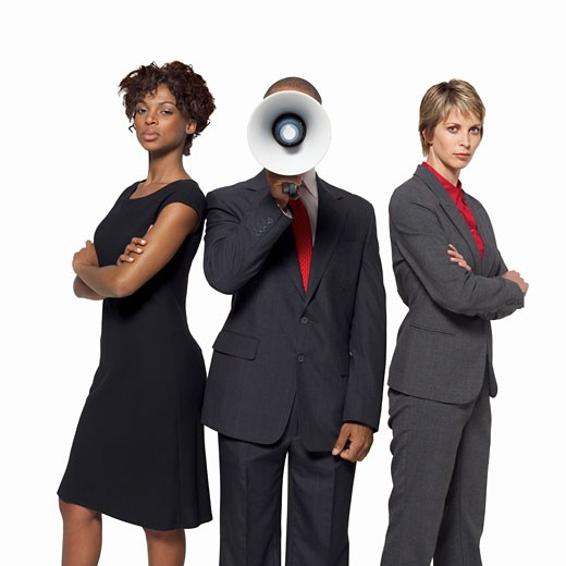 Businessman shouting through megaphone while two businesswomen stand beside him : Stock Photo