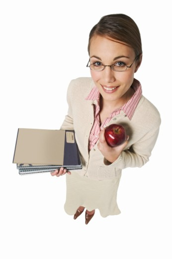 elevated view of a teacher carrying notepads and holding an apple : Stock Photo