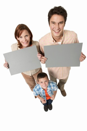 Portrait of parents and son (8-9) holding placards : Stock Photo