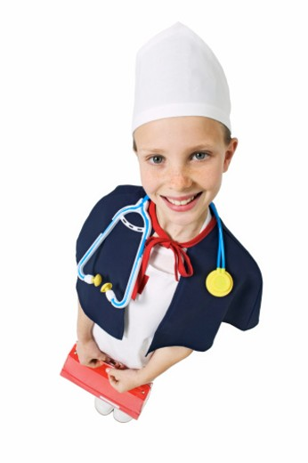 elevated view of a girl (11-12) wearing a nurse's uniform and holding a first aid kit : Stock Photo